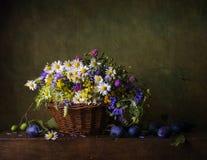 与野花的静物画在篮子 免版税库存照片