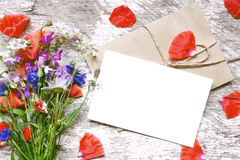 与野花花束的空白的白色与花瓣的贺卡和信封 库存图片