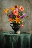 与野花花束的葡萄酒静物画在花瓶的 库存照片