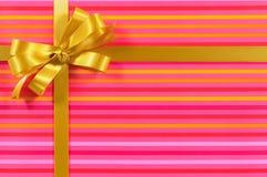与金丝带弓的桃红色糖果条纹礼物背景边界框架 图库摄影