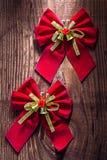 与金丝带的两把红色圣诞节弓和在老小的响铃 图库摄影