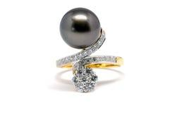 与金刚石和金戒指的黑暗的珍珠 库存图片