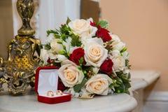 与金刚石的两只婚姻的金戒指在红色箱子在bride& x27附近; 红色和白玫瑰s花束  免版税库存图片