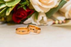 与金刚石的两只婚姻的金戒指是关于bride& x27; 红色和白玫瑰s花束  库存图片