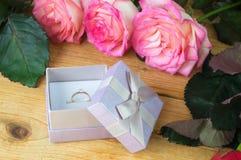 与金刚石的定婚戒指和在一木backgr的桃红色玫瑰 免版税库存图片
