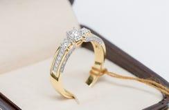 与金刚石的金戒指在白色背景的箱子 免版税库存照片