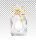 与金发光的丝带的塑料礼物袋子 免版税图库摄影
