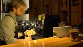 与金发的一有胡子的barista蒸在咖啡机器,舒适咖啡馆的牛奶 影视素材