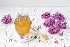 与金合欢的刺槐属蜂蜜在老木桌上开花 库存图片