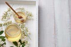 与金合欢的甜蜂蜜在木盘子开花 库存图片