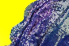 与金子、绿色和紫色衣服饰物之小金属片的抽象背景在黄色背景的织品 免版税库存图片