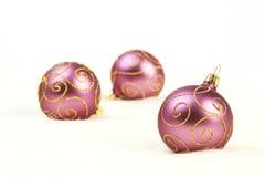 与金子的三个紫色圣诞节球在白色背景排行 图库摄影