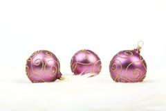 与金子的三个紫色圣诞节球在白色背景排行 免版税图库摄影