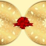 与金子颜色的两件圆水平的装饰品的背景图象与一把红色弓的 图库摄影