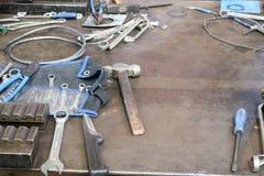 与金属制品工具,板钳,锤子,螺丝刀,钢丝钳,刀子,导线的铁桌在工厂,工厂 免版税库存照片