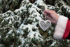 与金属圣诞节树玩具心脏的圣诞老人项目 库存图片