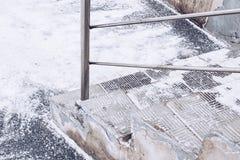 与金属扶手栏杆的危险石楼梯在雪下在冬天 图库摄影