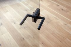 与金属把柄的玻璃门开放对有木地板的空的屋子 免版税库存照片