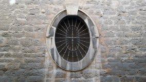 与金属格栅的老卵形窗口在一个石墙设置了 库存图片