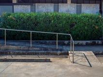 与金属棒的老难看的东西轮椅舷梯在空的汽车停车处附近 库存照片