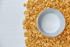 与金属碗的圆的框架用牛奶标示用玉米片 在一张木桌上驱散的玉米片 自由空间为 免版税图库摄影