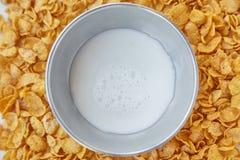 与金属碗的圆的框架用牛奶标示用玉米片 在一张木桌上驱散的玉米片 免版税库存照片