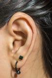 与金属耳环的人的耳朵特写镜头 库存图片