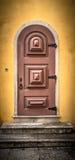 与金属铰链和锁的老木门在黄色墙壁上 T 免版税库存图片