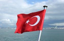 在伊兹密尔海湾背景的土耳其旗子 库存照片