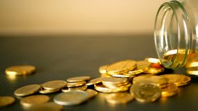与金币的特写镜头静物画在黑桌和转动的便士上 黄色硬币从瓶子落  影视素材