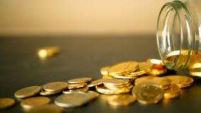 与金币的特写镜头静物画在黑桌和转动的便士上 黄色硬币从瓶子落  股票视频