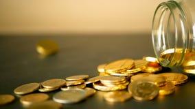 与金币的特写镜头静物画在黑桌和转动的便士上 黄色硬币从瓶子落  股票录像