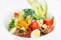 与金枪鱼、菠菜、芝麻菜、鳕、朝鲜蓟、鹌鹑蛋、鲕梨、西红柿、空泡和芝麻的新鲜的沙拉 库存图片