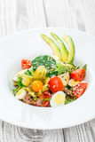 与金枪鱼、菠菜、芝麻菜、鳕、朝鲜蓟、鹌鹑蛋、鲕梨、西红柿、空泡和芝麻的新鲜的沙拉 库存照片