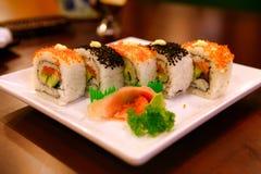 与金枪鱼和三文鱼的Uramaki卷在一块白色板材服务 北京瓷 图库摄影