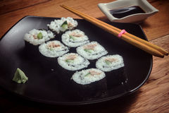 与金枪鱼和黄瓜的寿司卷在黑色的盘子 库存图片