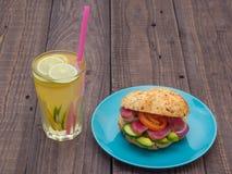 与金枪鱼的三明治在板材、菜和一杯柠檬水 图库摄影