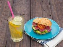 与金枪鱼的三明治在板材、菜和一杯柠檬水 免版税库存图片