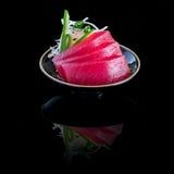 与金枪鱼的生鱼片在一个黑色的盘子 在与r的黑背景 免版税库存图片