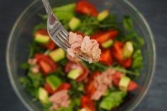 与金枪鱼肉片的一把叉子在与金枪鱼、鱼肉、芝麻菜和蕃茄,鲕梨的新鲜的沙拉 图库摄影
