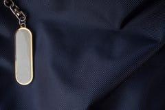 与金框架的白色标签在背景的黑背包 免版税图库摄影