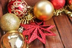 与金球的圣诞节装饰和在木背景的红色星 关闭 库存照片