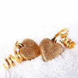 与金磁带的两心脏在雪 免版税库存照片