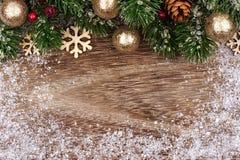 与金装饰品、分支和雪的圣诞节顶面边界 图库摄影