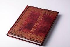与金装饰品的布朗皮革老笔记本 免版税库存照片
