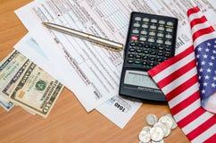 1040与金钱、笔和计算器,旗子的报税表 免版税库存照片