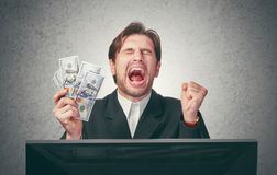与金钱在手中和计算机的愉快的商人 免版税库存图片