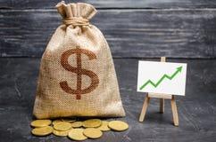 与金钱的袋子和绿色箭头在图 增长的赢利的概念和收支,增长的资本和增加 免版税库存照片