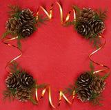 与金黄丝带的圣诞节装饰在红色纸的一个框架 库存图片