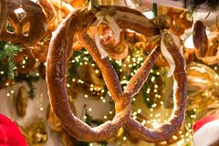 与金黄弓的椒盐脆饼在冷杉枝杈和椒盐脆饼背景 免版税库存照片